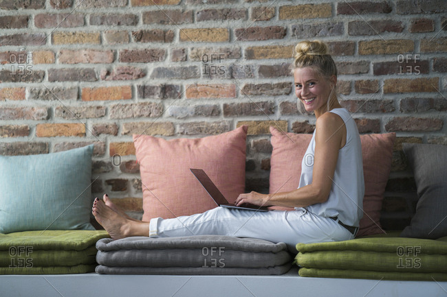 Mature woman sitting on couch- using laptop