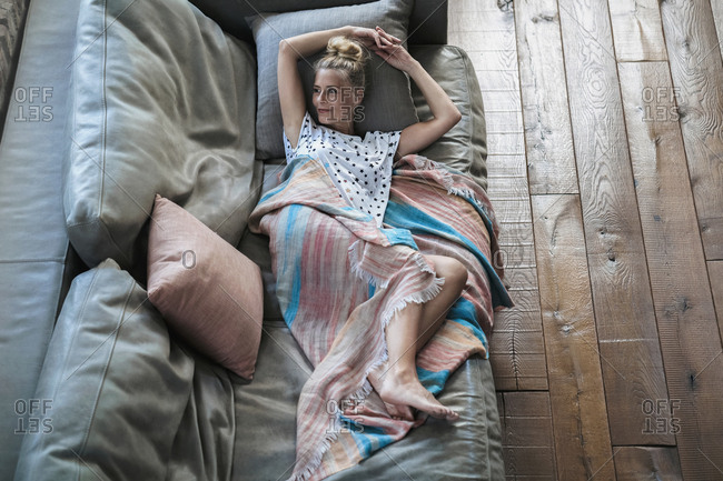 Woman relaxing on couch- wrapped in blanket