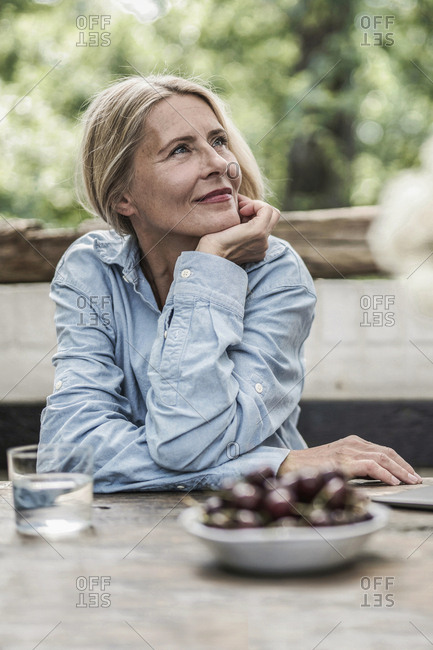 Mature woman sitting on terrace- with cherries on table