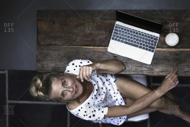 Woman sitting in kitchen- using laptop