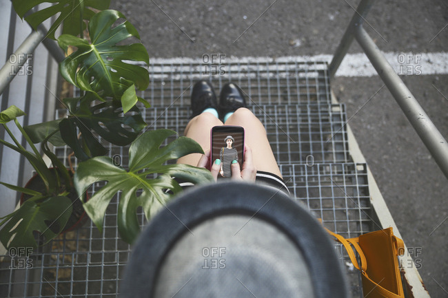Top view of woman sitting on stairs holding smartphone with her own