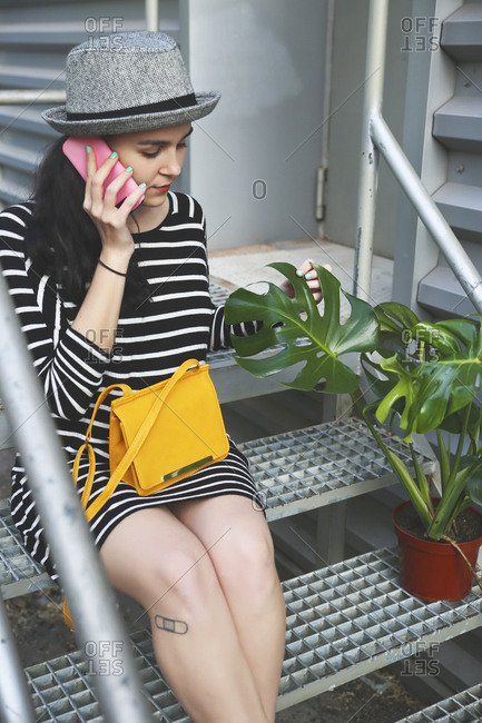 Young woman sitting on stairs telephoning with smartphone