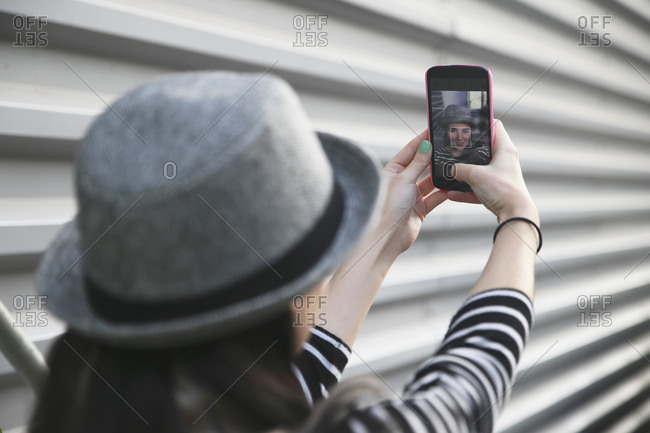 Back view of young woman taking a selfie with smartphone