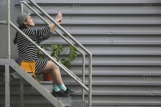 Young woman sitting on stairs taking a selfie with smartphone