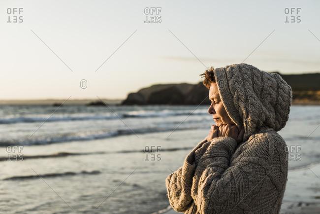 France- Crozon peninsula- woman wearing a cardigan on the beach at sunset
