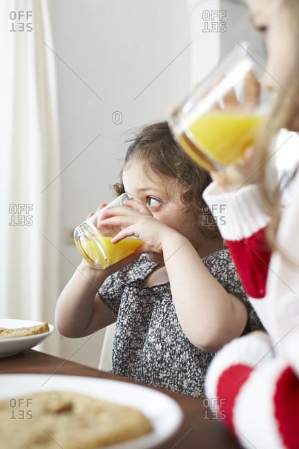 Little girls drinking orange juice at breakfast table