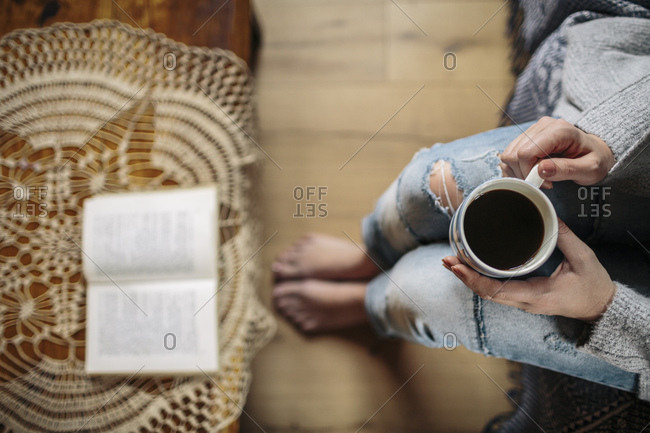 Young woman at home relaxing with cup of coffee and a book