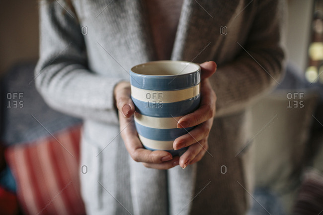 Young woman at home drinking cup of coffee