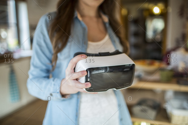 Young woman at home using Virtual Reality goggles