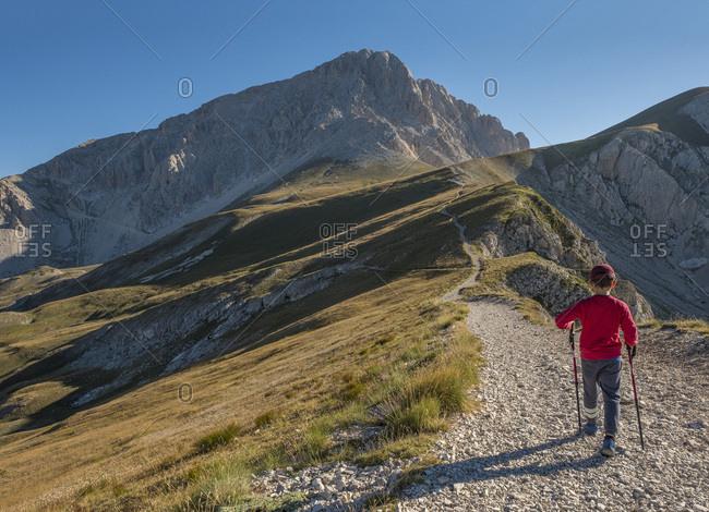 Italy- Abruzzo- Gran Sasso e Monti della Laga National Park- boy on hiking trail of Corno Grande