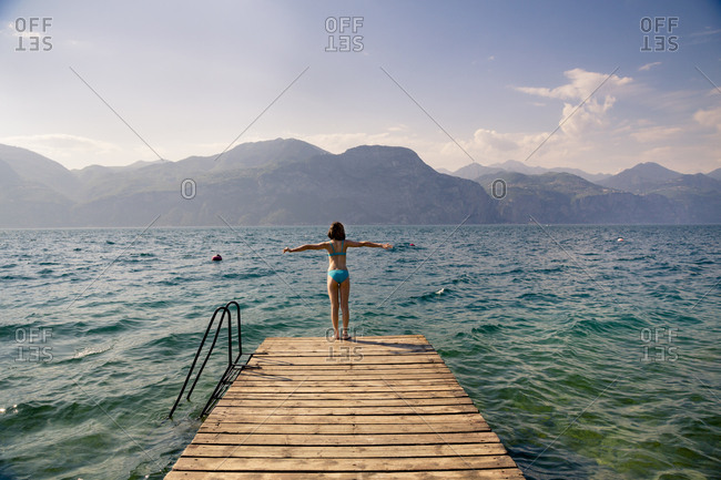 Italy- Brenzone- back view of girl standing on jetty