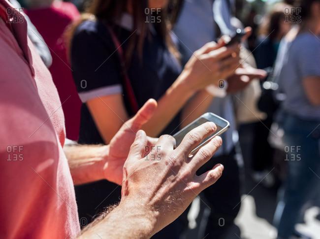 Man's hand using smartphone on the street