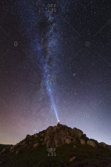 Spain- man illuminating the sky on a starry night with blue ray