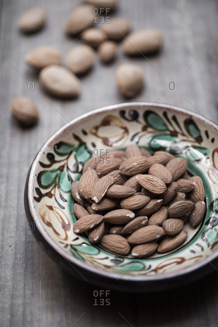 Almonds in hand-painted bowl on wood