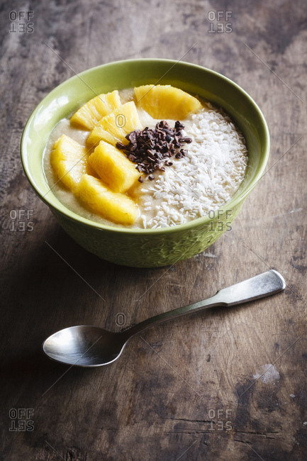 Bowl of fruit smoothie garnished with pineapple slices- coconut flakes and chocolate shaving