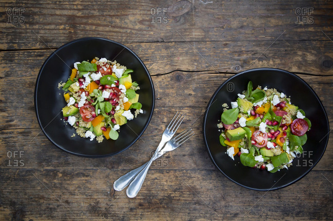 Salad bowls with lamb's lettuce- quinoa- yellow bell pepper- cocktail tomato- avocado- feta and pomegranate seeds