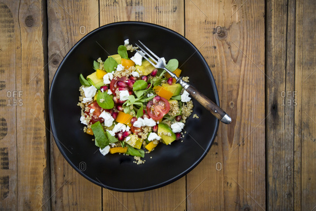Salad bowl with lamb's lettuce- quinoa- yellow bell pepper- cocktail tomato- avocado- feta and pomegranate seeds