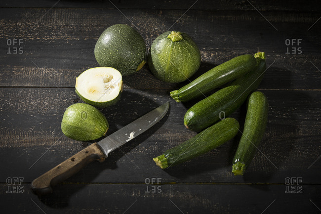 Eight ball squashes and courgettes on dark wood
