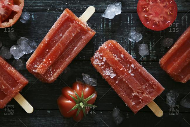 Tomato ice lollies on black wood