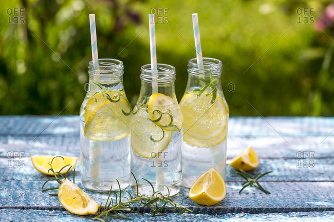 Slice of lemon and rosmary in water bottles- drinking straws