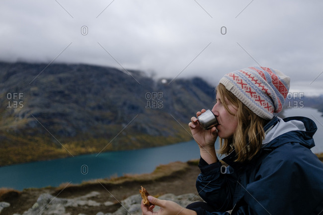 Woman drinking coffee and having food while sitting on cliff by river and mountains against cloudscape