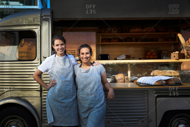Portrait of smiling female owners standing arm around outside food truck