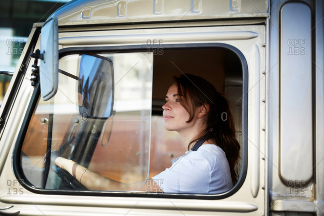 Young female owner driving food truck in city