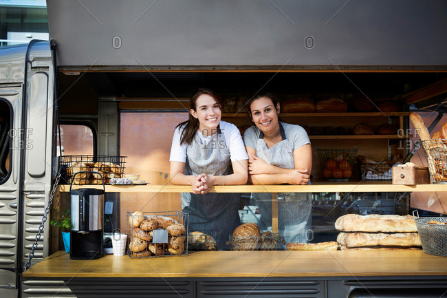 Portrait of smiling female owners in food truck parked in city