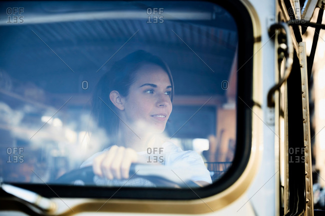 Young saleswoman looking away while driving food truck
