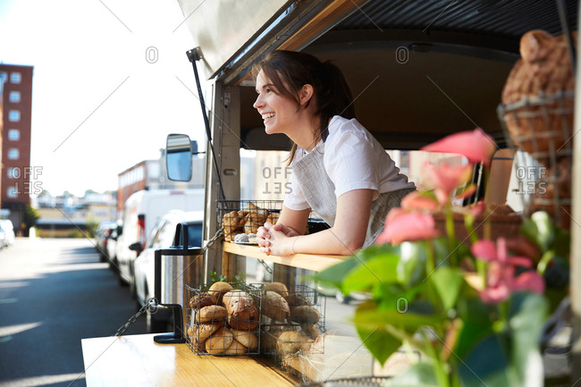 Smiling young female owner in food truck on city street