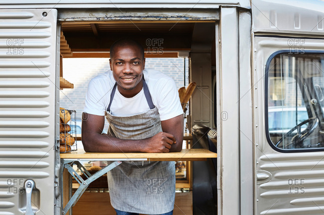 Portrait of confident mid adult male owner standing in food truck