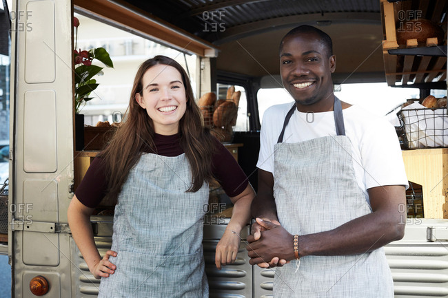 Portrait of smiling male and female owners standing outside food truck parked in city