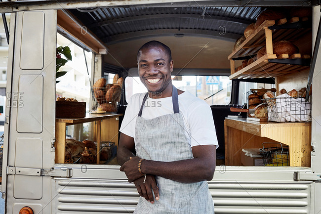 Portrait of smiling mid adult male owner standing outside food truck