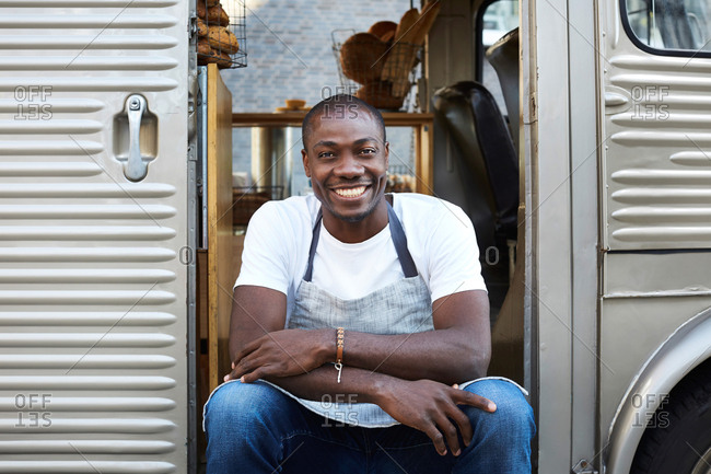 Portrait of smiling mid adult male owner sitting on doorway of food truck