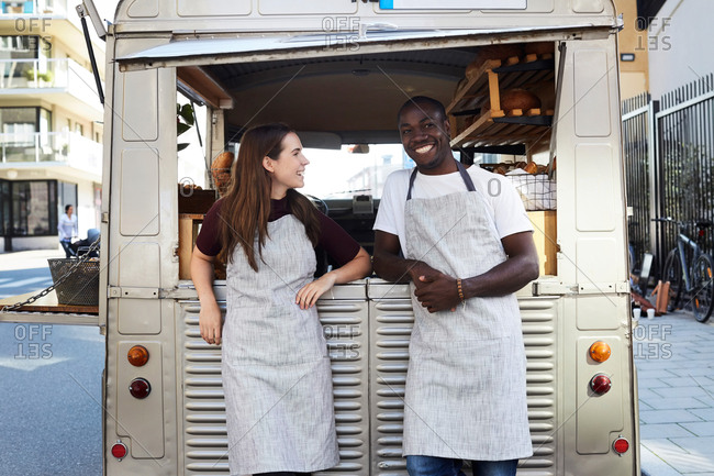 Smiling male and female owners standing outside food truck parked on city street