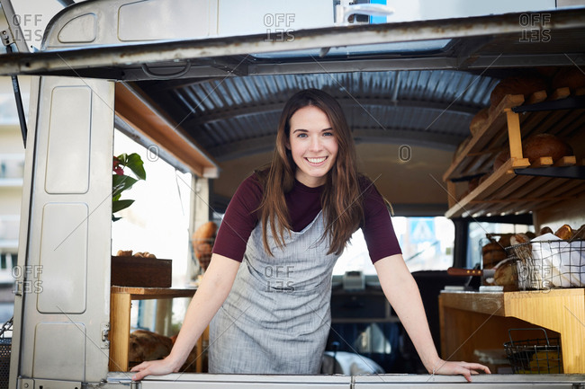 Portrait of smiling young female owner standing in food truck