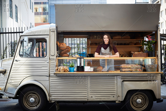 Portrait of smiling female owner standing in food truck parked on city street