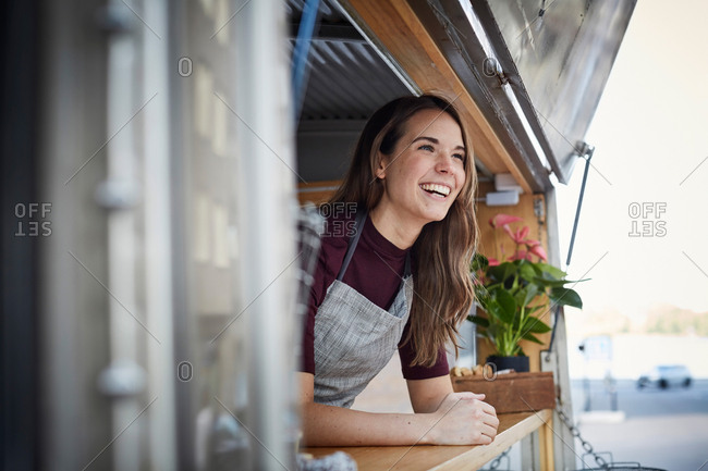 Smiling young woman looking away while standing in food truck at city