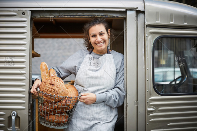 Smiling saleswoman carrying basket of fresh breads in food truck