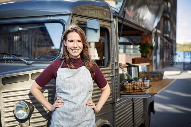 Portrait of smiling female owner standing hands on hips outside food truck in city
