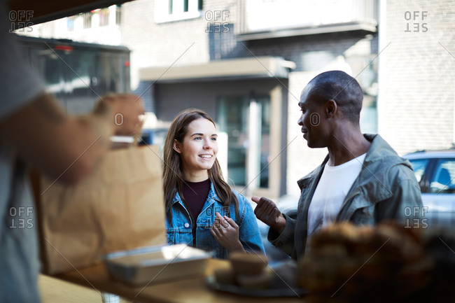 Multi-ethnic friends talking while salesman packing food at concession stand