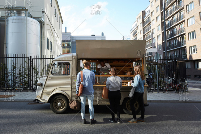Customers buying bread from salesman at food truck parked on city street