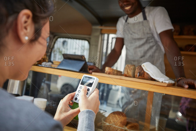 Mid adult woman using credit card reader to pay salesman at food truck