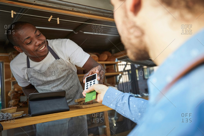 Man with credit card paying salesman at food truck