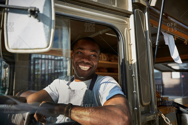 Smiling mid adult salesman looking away while driving food truck in city