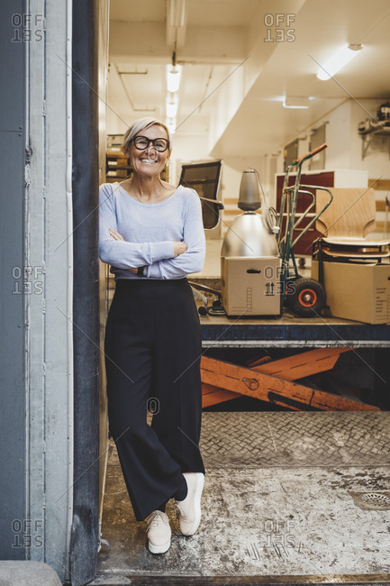 Full length portrait of smiling mature businesswoman standing arms crossed in new office