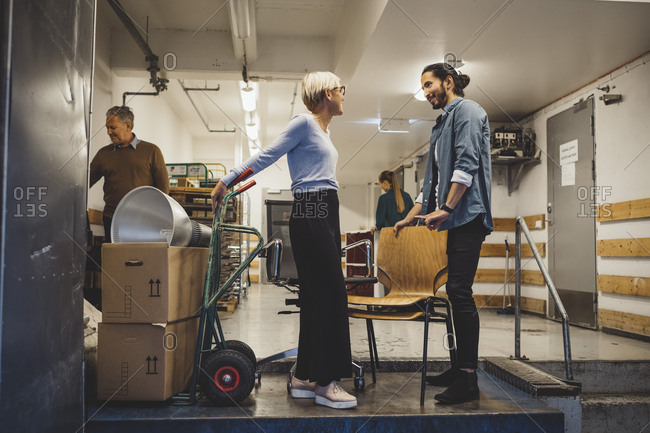 Businessman and businesswoman talking while moving into new office
