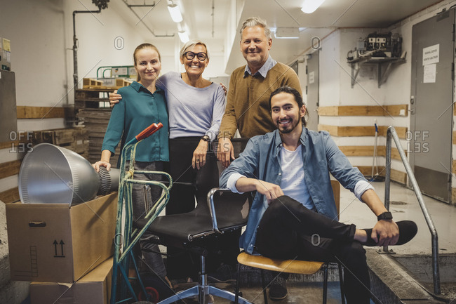 Portrait of smiling multi-ethnic business people with equipment in new office