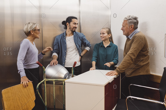 Multi-ethnic male and female business people with office equipment talking in elevator