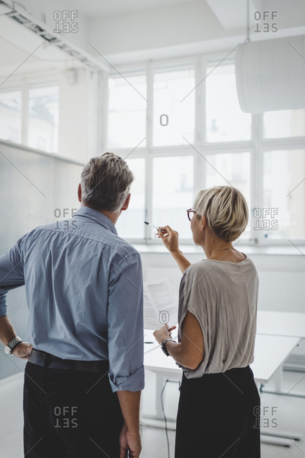 Rear view of mature businessman and businesswoman discussing in new office